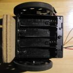 La trappe des batteries est fixée par une vis sur l'arrière du châssis.